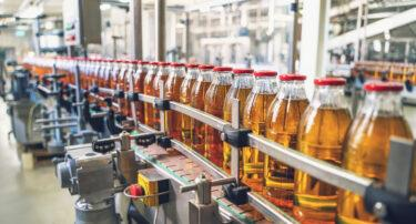 Conveyor belt with juice in glass bottles