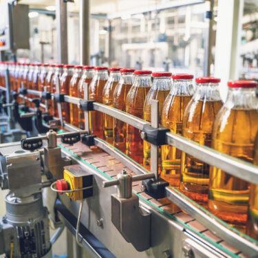 Conveyor belt with juice in glass bottles